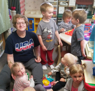 Tammy sits on the floor at her family-based child care surrounded by little kids.
