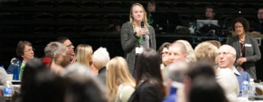 A student with a hand-held microphone addresses the crowd seated at tables in the gymnasium