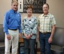 John, Diana and Ron are lined up in an office lobby in front of an Impact Innovation sign