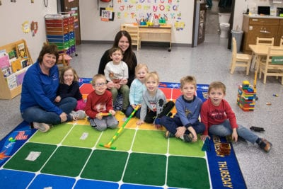 A group of preschool students sit on a colorful mat in a school room with two grown-ups