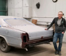 Rick is inside a shop, leaning with one hand on the sanded-down body of a classic car.