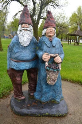Two gnomes dressed in blue and brown stand next to one another outdoors.