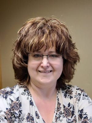A head shot of licensed clinical social worker Kerstin Cooley who owns Stepping Stone Therapy in Windom. Kerstin wears glasses and a patterned blouse in the photo.