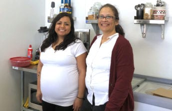 Karina and Debbie stand in front of a food prep area in the Taste in Time soda fountain.