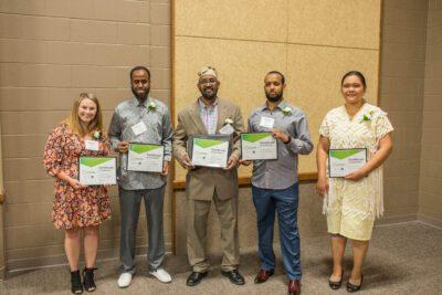 The entrepreneurs graduating from Elevate Business Academy stand shoulder-to-shoulder holding framed certificates.